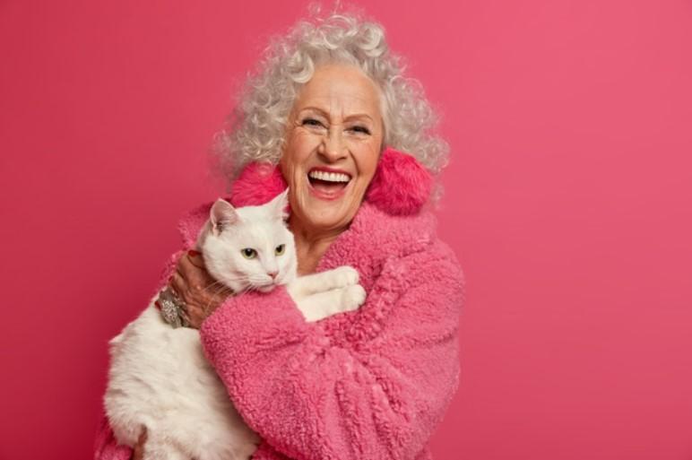 donna anziana abbraccia un gatto
